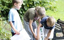Mehrere Kinder schauen bei einem OL-Posten die Karte an.