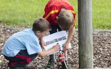Vor einem Pfosten kauern zwei Kinder über einer Karte.