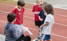 Eine Lehrerin erklärt mehreren Kindern, wie sie die OL-Karte lesen müssen.