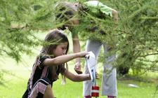 Zwei Mädchen lochen die Karte an einem Posten hinter einem Gebüsch.
