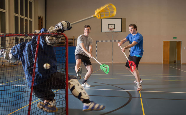 Drei Athleten in Aktion: Der Torhüter kann den Ball, der von einem Kollegen gespielt wurde nicht fangen.