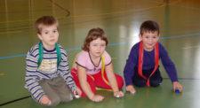 3 Kinder sitzen am boden in einer Reihe unsd spielen mit Flaschendeckeln.