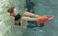 Una partecipante è seduta in acqua con i piedi posati su una tavoletta.