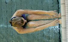 Una donna è in posizione dorsale, gambe raccolte e piedi appoggiati contro la parete della piscina.