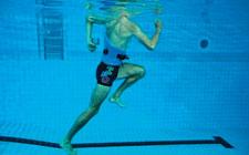 Un uomo esegue un esercizio in acqua poco profonda. Solleva la gamba sinistra accompagnando il movimento con le braccia.