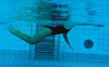 Une athlète nage en crawl waterpolo avec des battements de jambes du dauphin.