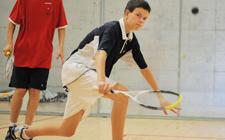 Zwei Kinder beim Squashspiel, eines nimmt den Ball ab, das andere schaut zu.