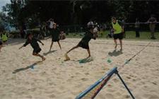 Situazine di gioco sulla spiaggia. Un bambino afferra una palla mentre un altro inizia a correre.