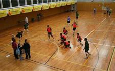 Weite Aufnahme: Ein Spieler wirf gerade ab während die anderen zuschauen und zu verteidigen versuchen.