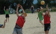 Spiel auf Sand. Ein Kind versucht, einen Ball abzufangen, der über ihn fliegt. Ein anderes fängt den Ball dahinter auf.