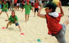 Kinder spielen auf Sand Tchoukball, ein Kind wirft gerade ab.