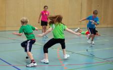 Mehrere Kinder in der Turnhalle in Action: am Rennen, am Ausweichen, etc.
