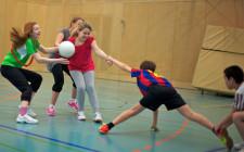 Vier Jugendliche zerren aneinander, während eine versucht, einen Ball zu beschützen.