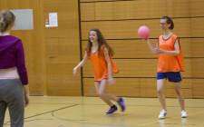 Ein Mädchen hat einen Ball und versucht, eins aus einem anderen Team abzuwerfen.