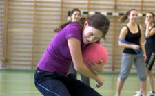 Junge Frau mit Ball in der Hand versucht, sich vor einem heranfliegenden Ball zu schützen.