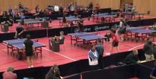Photo d'une compétition dans une salle comprenant plusieurs tables.