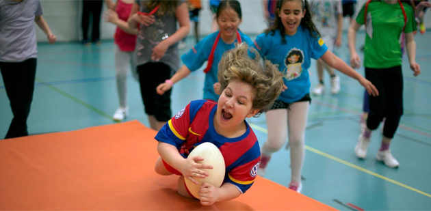 Ein Junge hält einen Rugby-Ball in der Hand und springt auf eine dicke Matte, andere jagen ihm nach.