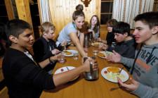 Jugendliche sitzen am Tisch und teilen sich das Essen.