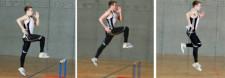 Junger Athlet, der über tiefe Hürden springt.