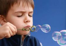 Kleines Kind, das Luftblasen macht.