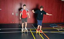 Due ragazzi avanzano in una palestra pedalando su un asse sottile munito di rotelle laterali.