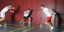 Drei Jugendliche mit Badmintonschlägern versuchen, diese im Kreis nicht fallen zu lassen.