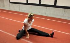 Frau bei einer Stretching-Übung am Boden.