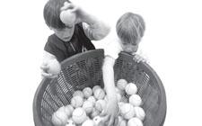 Dei bambini lanciano delle palline in un grande cesto di vimini