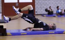 Un ragazzo è steso su un tappetino e solleva il bacino. Una gamba appoggiata ad un elemento di cassone e l'altra la tira verso di sé.