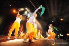 Delle ragazzine su un palcoscenico ballano tenendo un fazzoletto colorato in mano.