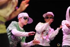 Dei bambini con un cappellino sulla testa e degli occhiali da sole battono il ritmo con le mani su un palcoscenico