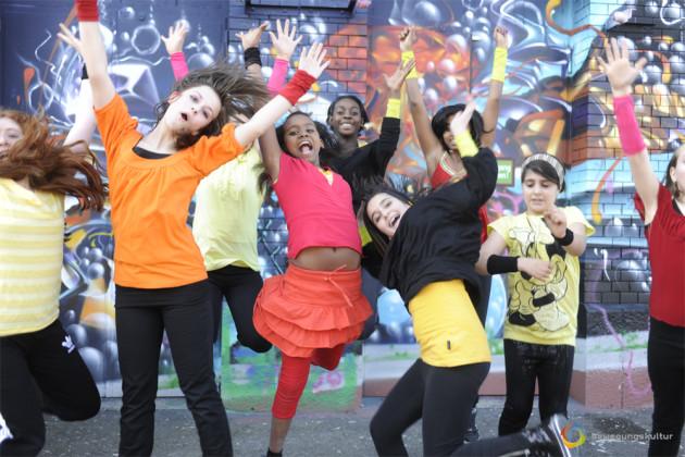 Junge Mädchen stehen vor einer besprayten Wand und Tanzen.