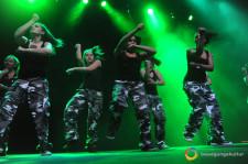 Un gruppo di ragazze balla su un palcoscenico illuminato di verde