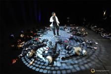 Un ragazzo si trova su un palcoscenico circondato da altri ballerini sdraiati attorno a lui