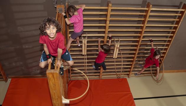 Kinder tummeln sich an der Sprossenwand.