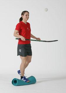 Une athlète est en équilibre sur une jambe sur un support instable et dribble une balle d'unihockey avec un e canne d'unihockey.