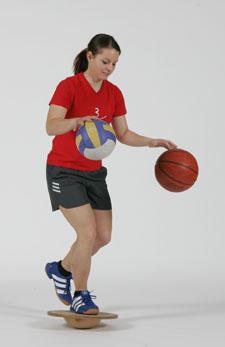 Une athlète est en équilibre sur un ballon et fait rebondir un ballon de basketball et un ballon de volleyball.