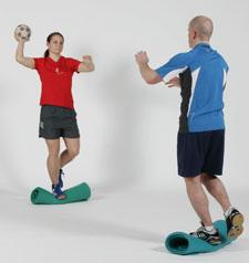 Deux athlètes sont en appui sur une une jambe sur une surface instable et se font des passes.