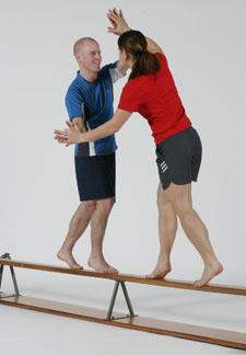 Deux athlètes sont en équilibre sur un banc suédois retourné et essaient de se déséquilibrer.