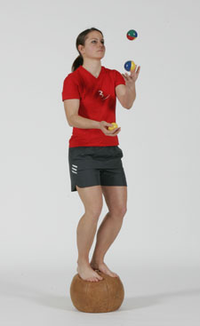 Une athlète est debout sur un ballon lourd et jongle avec trois balles.