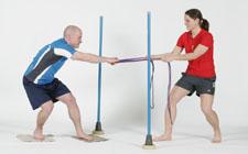 Un athlète est debout sur deux morceaux de tapis et se fait tracter par une collègue.