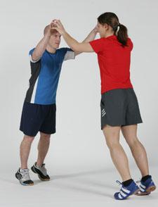 Deux athlètes se tiennent sur la pointe des pieds et se touchent du bout des doigts.