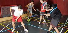 Dei giovani praticano diversi sport contemporaneamente in una piccola area della palestra: calcio, unihockey, ecc.