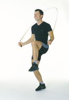 Un athlète saute à la corde en tirant le genou à hauteur des hanches.