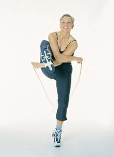 Après avoir sauté sur la corde, une athlète lève un genou et croise les bras