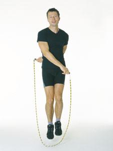 Un athlète saute en croisant les bras: un devant le corps, l'autre derrière le corps.