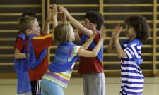 Dei bambini si danno il cinque con entrambe le mani dopo aver segnato un punto.