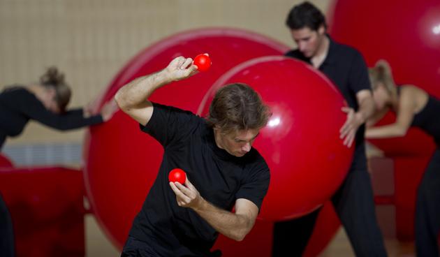 Junger Mann im Vordergrund mit zwei kleinen roten Bällen, im Hintergrund mehrere Akteure mit grossen roten Bällen.