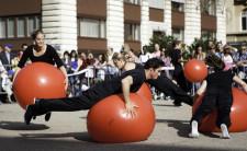 Männer und Frauen walzen sich auf riesigen Bällen auf einem Platz mitten in einer Stadt.