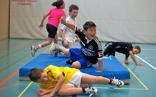 Dei bambini giocano in una palestra. Due sono sdraiati per terra, uno si trova su un tappetino e alza la mano, mentre altri due corrono